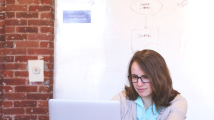 person sitting at laptop in front of whiteboard