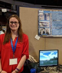 Image of Emily Blackwood standing in front of her Presentation at the UMaine Student Symposium. She is wearing a red long sleeve shirt.
