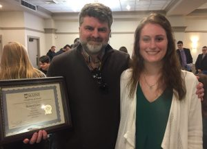 Dr. Rick Corey and Emily Blackwood holding up Rick's Student Supervisor Award. Rick is wearing a brown fleece and Emily is wearing a green shirt and white sweater.