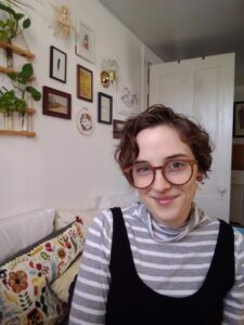 Hannah wears a grey and white striped turtleneck and a black overall dress. She has glasses and short curly hair and is sitting in front of embroidered pillows and a gallery wall of pictures and plants.