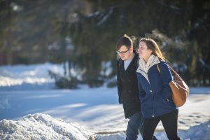 male and female walking outside on campus in Winter