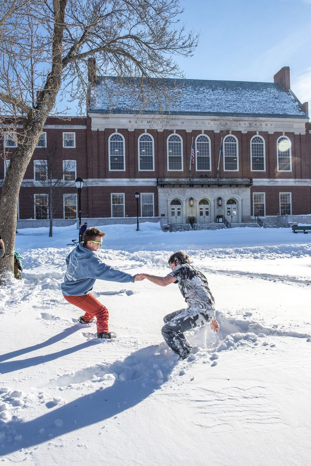student getting up out of the snow in front of Fogler Libary
