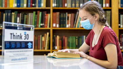 student reading in library with mask on