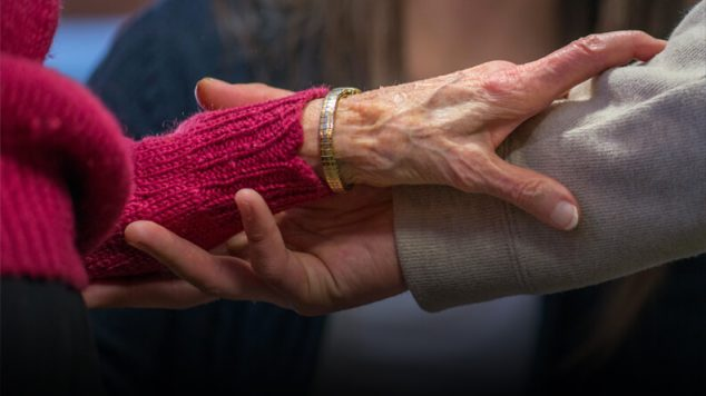 Elderly hand reaching for younger hand