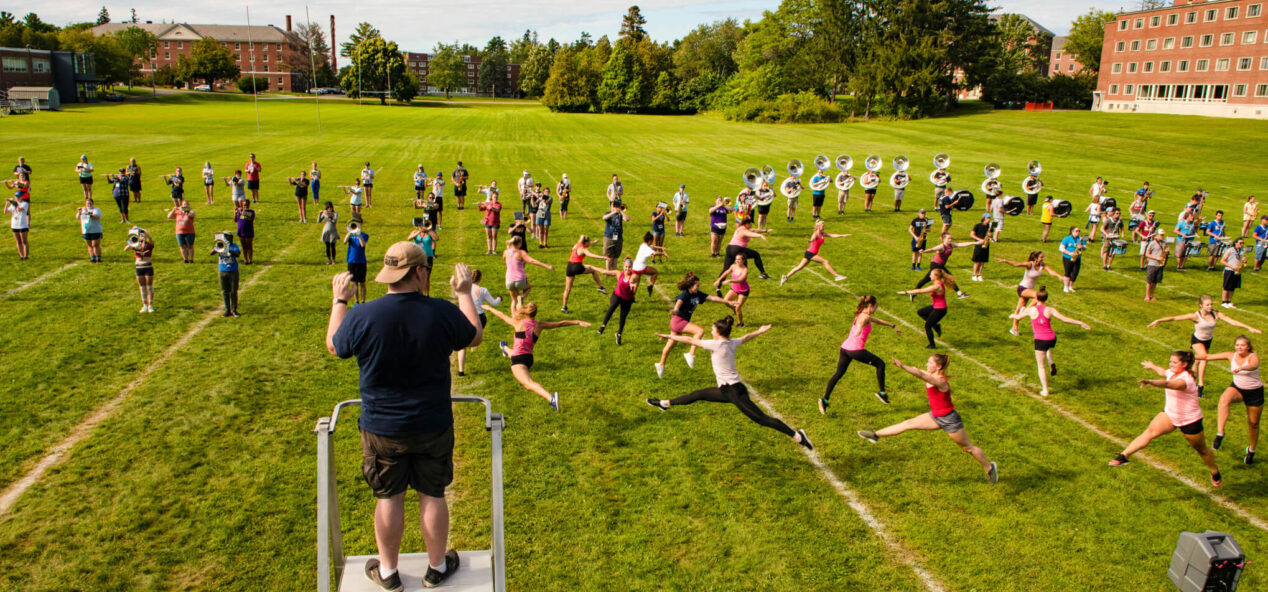 Pride of Maine Marching Band practicing in a field on campus