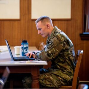 Man in military attire working on laptop