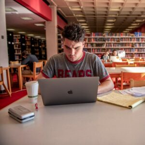 Man working on laptop in library