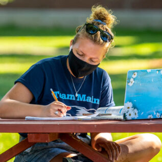 Woman studying at a picnic table on campus