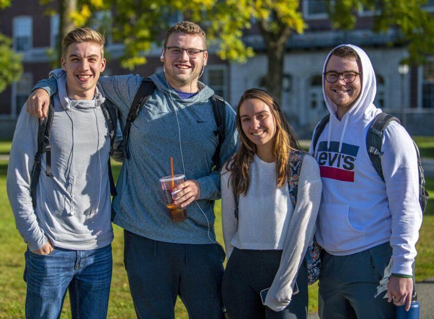 Four students stand outside Fogler Library
