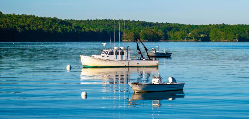 Three small boats in the water off the coast of Maine