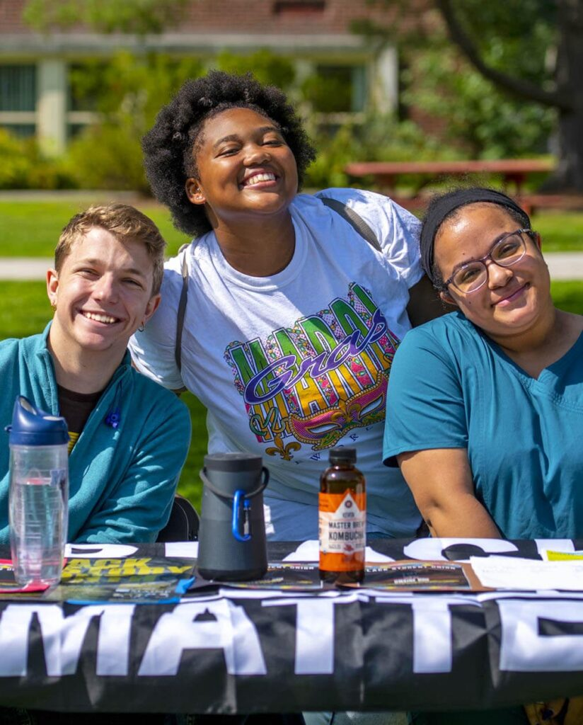 Three students smile while sitting at a table on UMaine's Mall