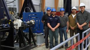 ORPC and UMaine staff members standing nexts to tidal energy technology