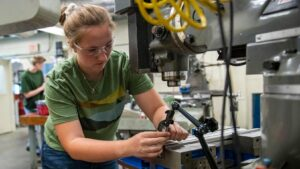 A woman works in UMaine's Advanced Manufacturing Center